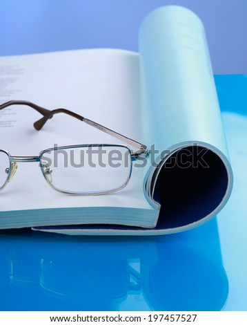 Glasses lying on a book - stock photo