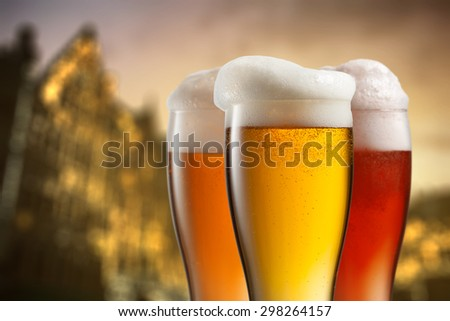 Glasses of beer against blurred european city with beautiful lights on background at evening - stock photo