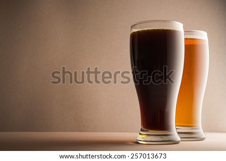 Glasses of beer on wood table - stock photo