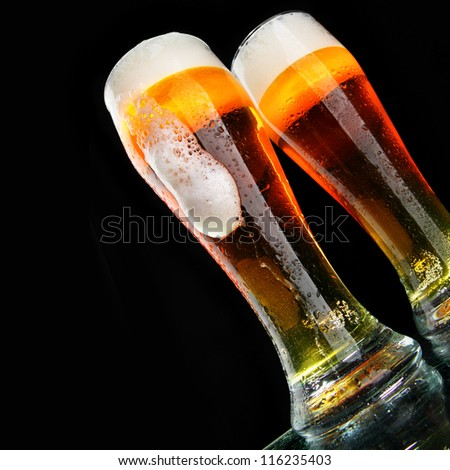Glasses of beer with froth over black background - stock photo