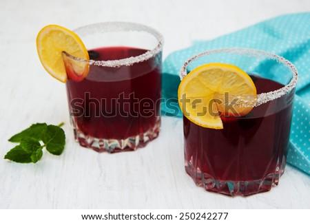 Glasses of blackberry lemonade on a old white wooden background - stock photo