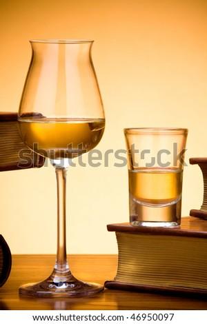 Glasses of brandy near books. - stock photo