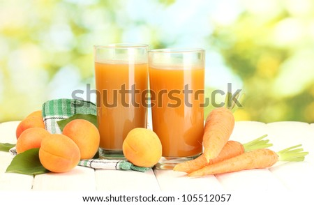 glasses of carrot and  apricot juice on white wooden table on green background - stock photo