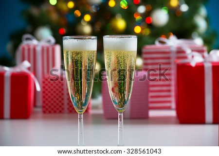 Glasses of champagne and Christmas gifts on the background - stock photo