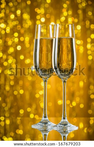 glasses of champagne on a gold background - stock photo