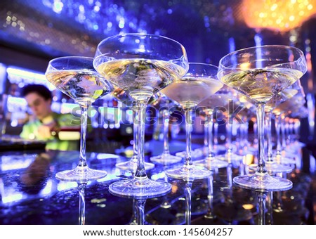 Glasses of champagne on bar counter with barman professional, which making cocktail drinks in background, soft focus - stock photo
