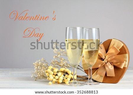 glasses of champagne with gift and herbarium on wooden table on grey background with inscription - stock photo