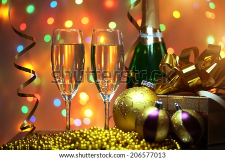 Glasses of champagne with gift box. background of lights - stock photo