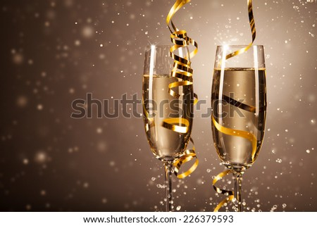 Glasses of champagne with ribbons and bubbles around. Concept of celebration - stock photo