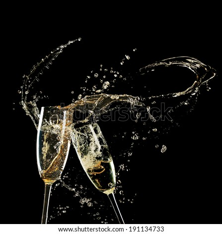 Glasses of champagne with splash, on black background - stock photo