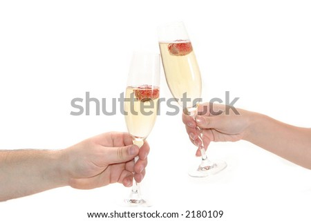 glasses of champagne with strawberry in hands on black background - stock photo
