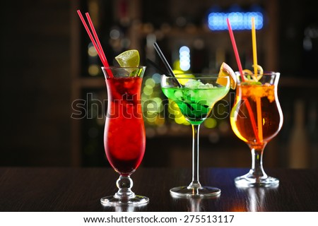 Glasses of cocktails on bar background - stock photo