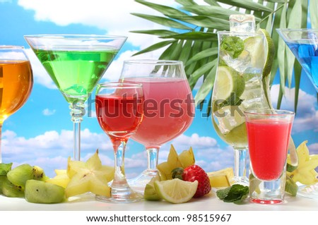 Glasses of cocktails on table on blue sky background - stock photo