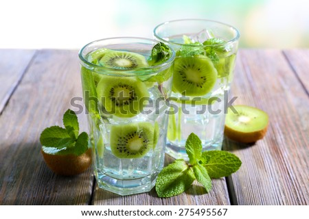 Glasses of cocktails on wooden table on bright blurred background - stock photo