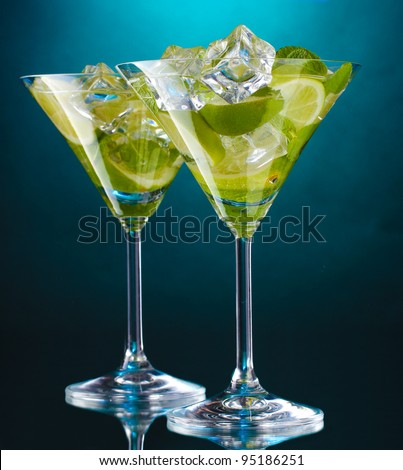 glasses of cocktails with lime and mint on blue background - stock photo