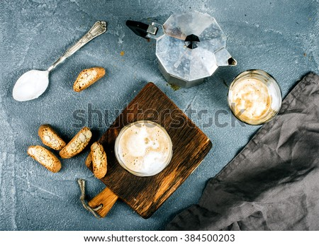Glasses of coffee with ice cream on rustic wooden board, steel Italian Moka pot over grey concrete textured background, top view - stock photo
