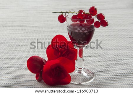 glasses of cordial and fruit of currant and flower - stock photo