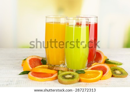 Glasses of different juice with fruits and mint on bright background - stock photo