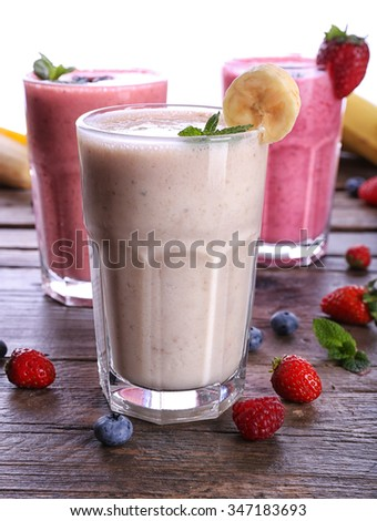 Glasses of fresh cold smoothie with fruit and berries, isolated on white - stock photo