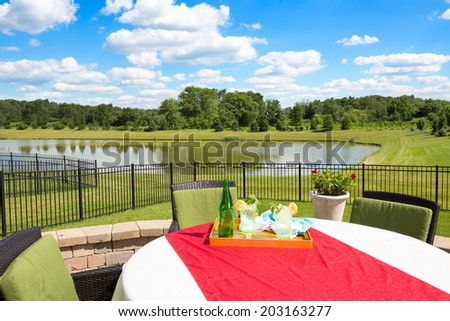 Glasses of fresh iced water garnished with fresh mint and lemon on a garden table covered in a colorful red cloth overlooking a tranquil pond and lush green countryside - stock photo