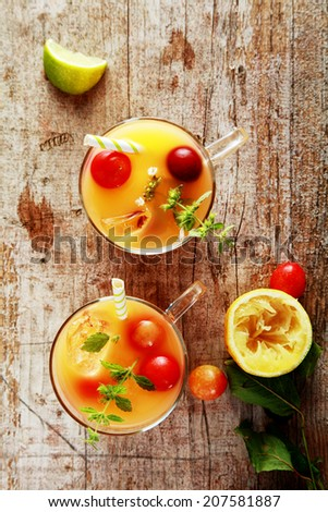 Glasses of fresh summer fruit cocktail with blended fruit juices garnished with fresh cranberries and herbs on a rustic wooden table, overhead view - stock photo