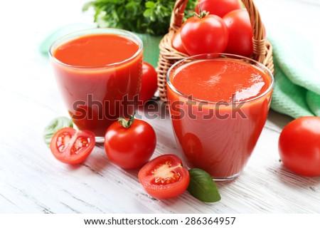 Glasses of fresh tomato juice on wooden table, closeup - stock photo