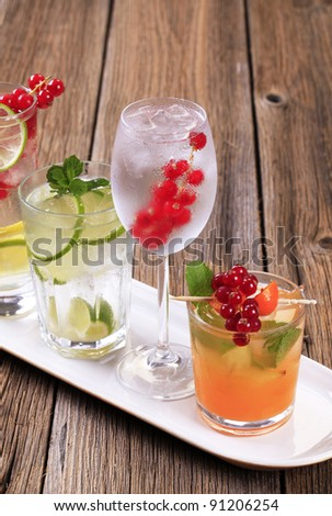 Glasses of iced drinks garnished with fresh fruit  - stock photo