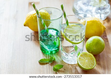 Glasses of lemonade with striped paper straws with mint leaves and fresh lime - stock photo
