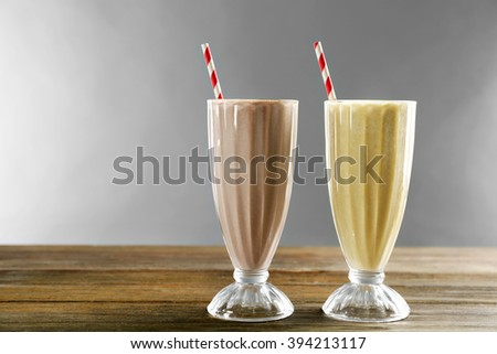 Glasses of milk cocktail on grey background - stock photo