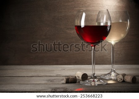 Glasses of red and white wine with corks on rustic wooden background with copy space. - stock photo