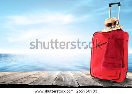 glasses of red hat and red suitcase with red towel  - stock photo