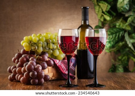 Glasses of red wine and bottle on wooden table - stock photo