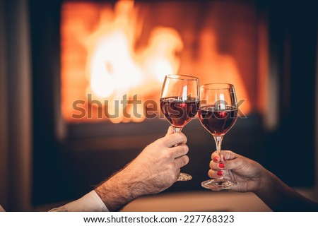 glasses of red wine and romantic fireplace - stock photo