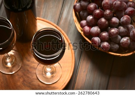 Glasses of red wine with red globe grapes and a bottle of wine, photographed on dark wood with natural light (Selective Focus, Focus on the rim of the wine glass) - stock photo