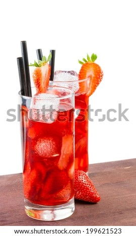 glasses of strawberry cocktail with ice on old wood table and a white background - stock photo