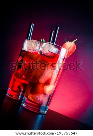 glasses of strawberry cocktail with ice on wood table on blue and pink light, disco club atmosphere - stock photo