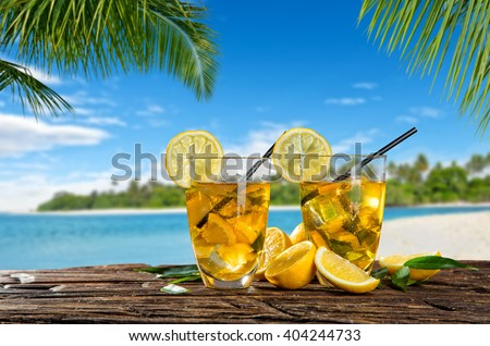 Glasses of summer ice tea drink on beach - stock photo