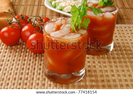 Glasses of tomato juice with tomatoes on the vine - or a Bloody Mary cocktail - stock photo
