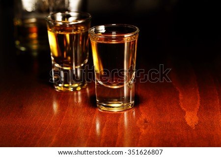 glasses of whiskey shots on wooden surface - stock photo
