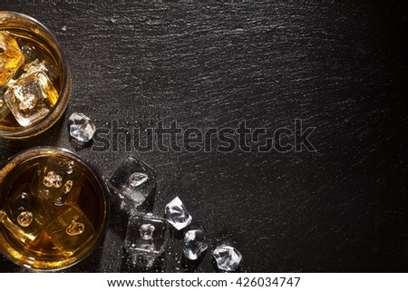 Glasses of whiskey with ice on black stone table. Top view with copy space - stock photo