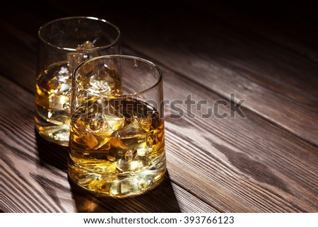 Glasses of whiskey with ice on wooden table with copy space - stock photo
