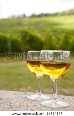 Glasses of white Pinot wine in front of a vineyard in Alsace, France - stock photo
