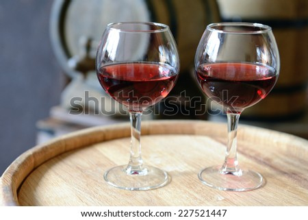 Glasses of wine in cellar with old barrels  - stock photo