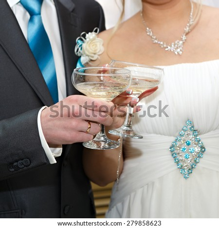 Glasses of wine in the hands of the bride and groom at a wedding party. - stock photo