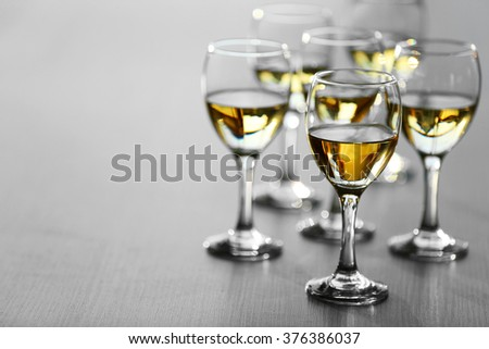 Glasses of wine on wooden blurred background - stock photo