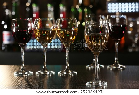 Glasses of wine with bar on background - stock photo