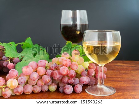glasses of wine with grape on a wooden table - stock photo