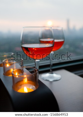 Glasses of wine with romantic setting - stock photo