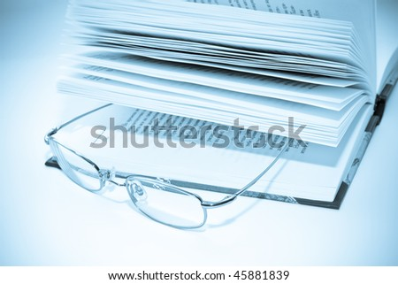 glasses on a book isolated on white background - stock photo