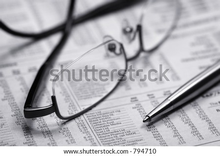 Glasses on a newspaper with a pen. Black and white - stock photo